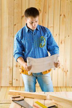 carpenter looks on blueprint