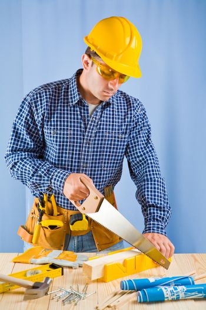 carpenter works with handsaw
