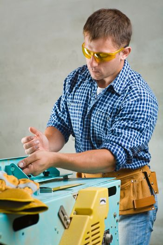 men works on woodworking mashine