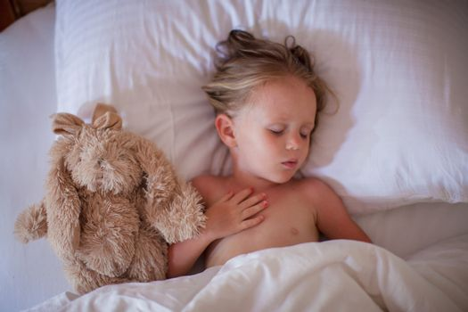 Adorable toddler taking a nap with favorite toy