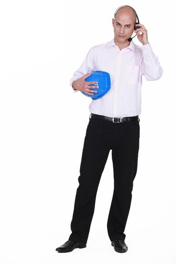 full-length portrait of businessman with headset holding hard hat