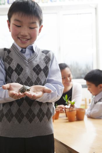 Schoolboy holding a little turtle in his hands, Beijing