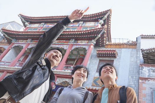 Three people sightseeing, looking and pointing.