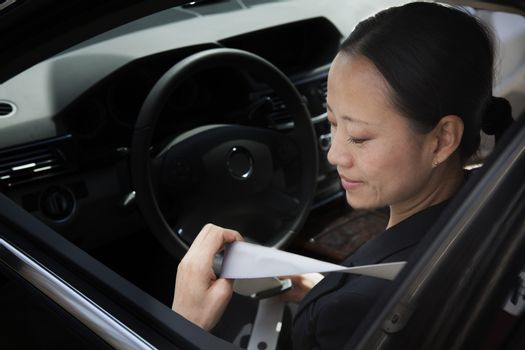 Mature businesswomen in car fastening seatbelt.