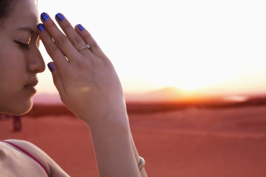 Serene young woman with eyes closed and hands together in prayer pose in the desert in China, side view