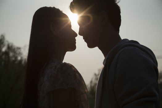 Silhouette of young couple very close to each other, sunbeam and lens flare