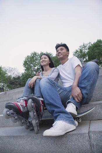 Young happy couple sitting and resting on concrete steps outside with a skateboard and roller blades