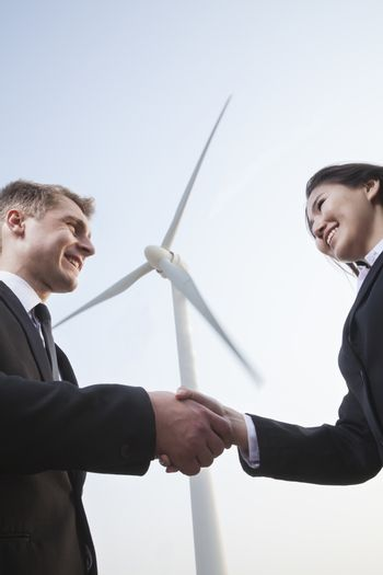 Two smiling young business people shaking hands in front of a wind turbine