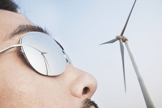 Close up of young mans face with the reflection of the wind turbine in his sunglasses