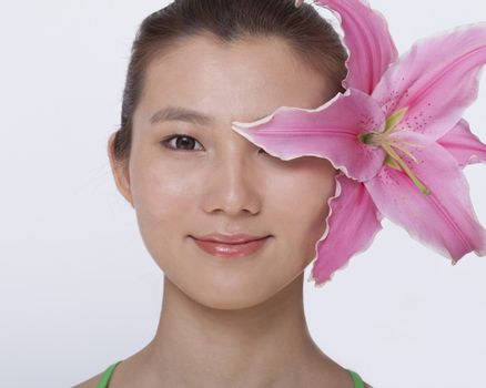 Portrait of young, smiling, beautiful woman with a large pink flower tucked behind her ear, studio shot