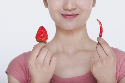 Young woman smiling and holding opposites, a strawberry and a chili pepper, in each hand