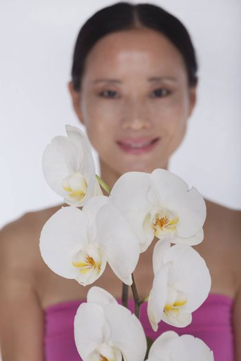 Smiling woman standing behind a bunch of beautiful  white flowers, studio shot