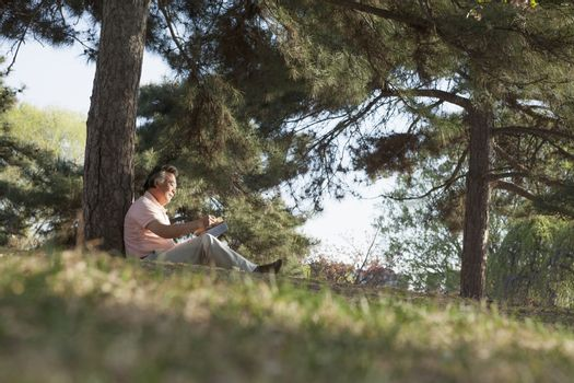 Senior man relaxing under a tree and reading a book in a park in the springtime, Beijing