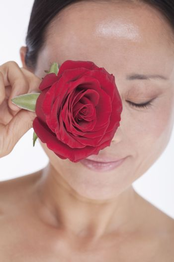 Smiling, beautiful, shirtless woman holding a red rose to her eye, studio shot