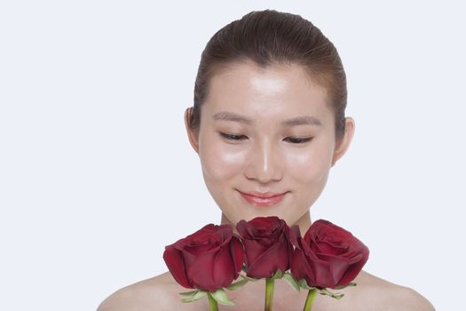 Young, beautiful, smiling woman looking down at a bunch of red roses, studio shot