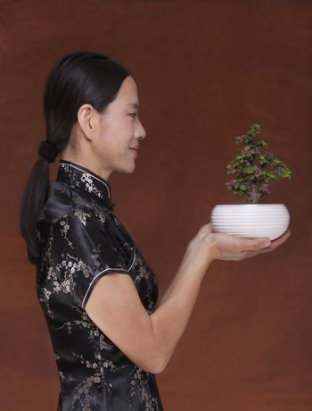 Side view of woman in traditional clothing holding a small plant in a flower pot, studio shot