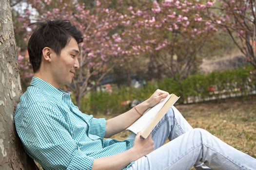 Smiling young man leaning on a tree and enjoying his book, outdoors in a park