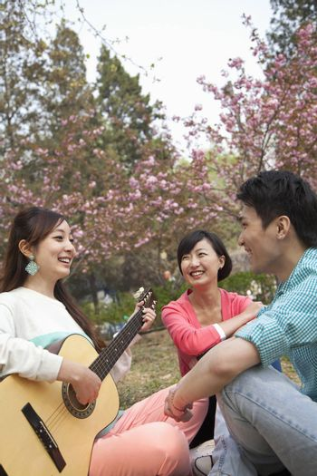 Young happy friends hanging out in the park in springtime, playing guitar