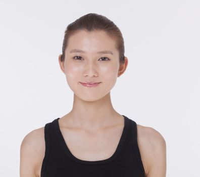 Portrait of smiling beautiful young woman in a black tank top, studio shot