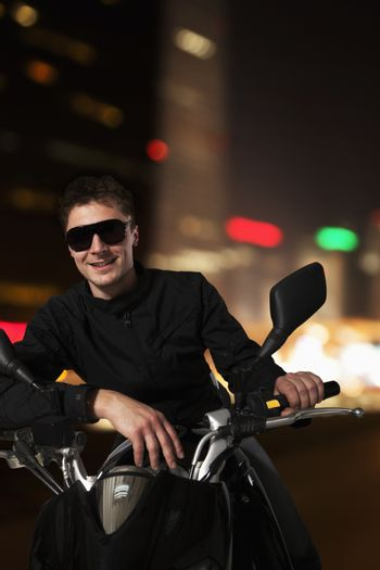 Young smiling man in sunglasses sitting on his motorcycle at night in Beijing