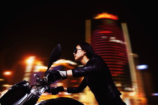Beautiful young woman riding motorcycle in sunglasses through the city streets at night