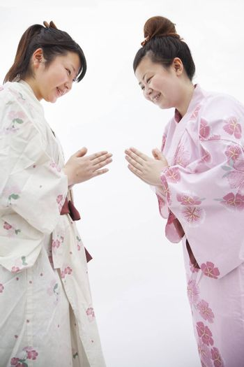 Two young smiling  woman in Japanese kimonos bowing to each other, studio shot