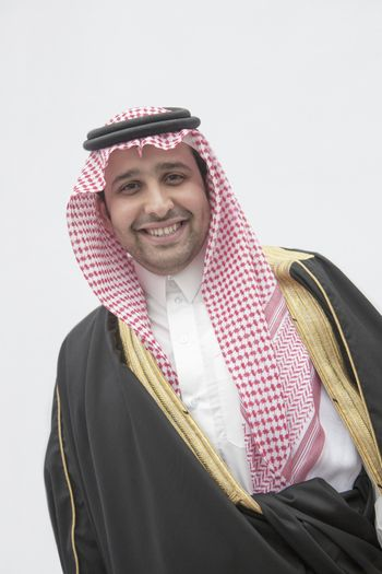 Portrait of smiling young man in traditional Arab clothing and Kaffiyeh, studio shot