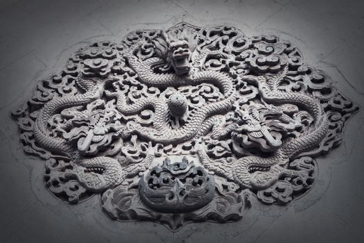 Ornate low relief sculpture of dragon on wall.