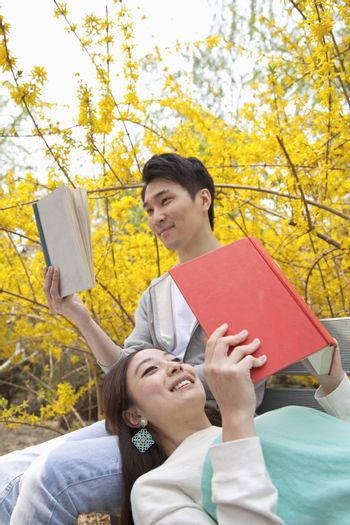 Young happy couple lying and sitting on a park bench enjoying reading their books, outdoors in springtime