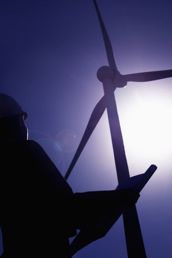 Young female engineer holding open blueprints and checking wind turbines on site, silhouette, low angle view
