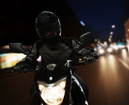 Young Man riding a motorcycle at night through the streets of Beijing