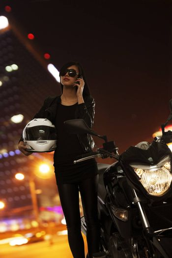 Young woman in sunglasses talking on the phone and standing beside her motorcycle at night in Beijing