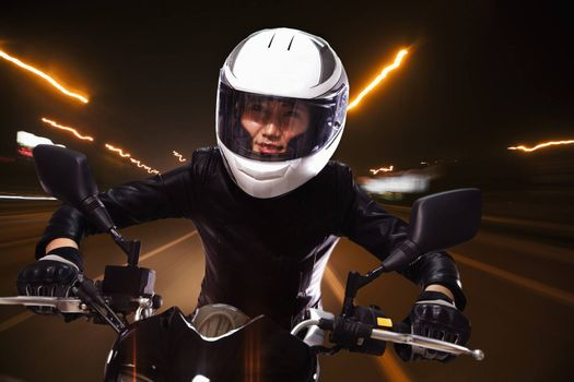 Young woman riding a motorcycle through the streets of Beijing, light trails