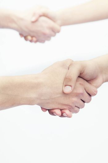 Four young people shaking hands, close-up, studio shot