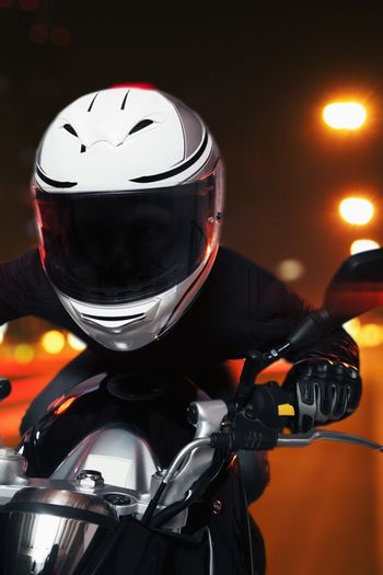 Young man riding a motorcycle at night through the streets of Beijing, front view