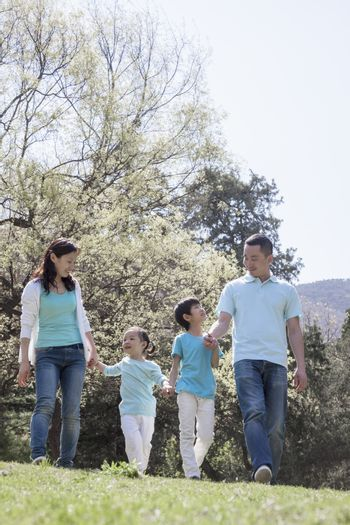 Family holding hands, walking in park.