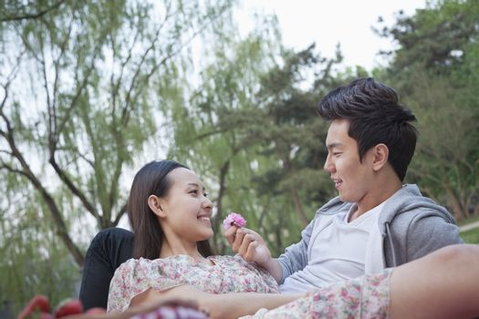 Smiling couple in love having a picnic in the park, lying down on the blanket and holding a flower blossom