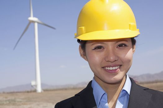 Portrait of young smiling female engineer checking wind turbines on site