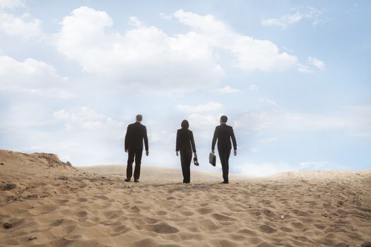 Three young business people walking through the desert, rear view, distant