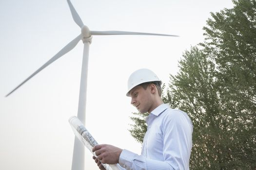 Young male engineer in a hardhat looking down at a blueprint in front of a wind turbine