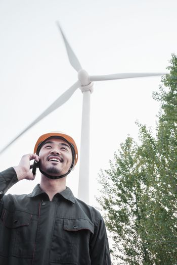 Young smiling male engineer in a hardhat on the phone beside a wind turbine