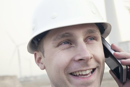 Young smiling male engineer in a hardhat on the phone beside a wind turbine, close-up