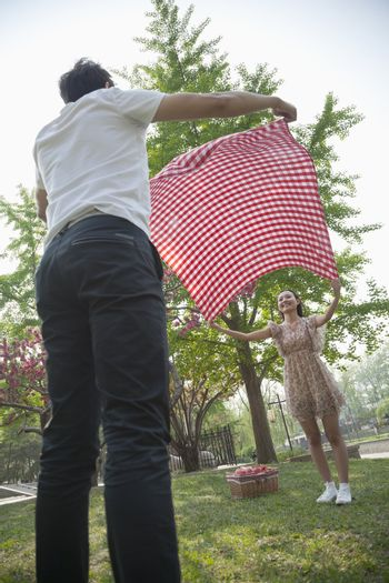 Two friends opening up a checkered blanket and getting ready to have a picnic in the park