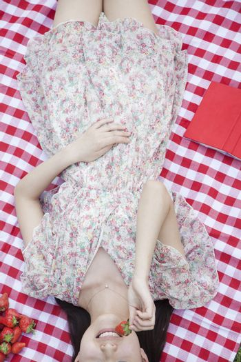 Midsection of a young woman lying on her back on a checkered blanket eating strawberries