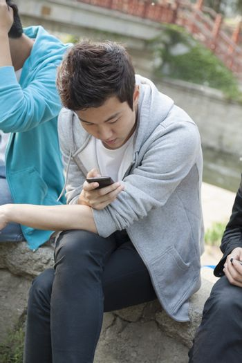 Young man in a gray hooded sweatshirt looking down at his phone and texting outdoors