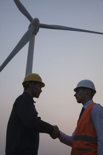 Two young male engineers standing beside a wind turbine at sunset and shaking hands
