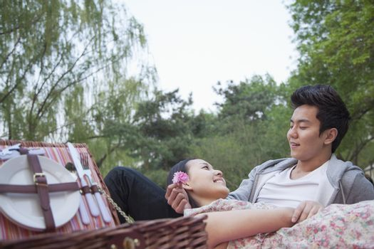 Smiling couple in love having a picnic in the park, lying down on the blanket with picnic basket open