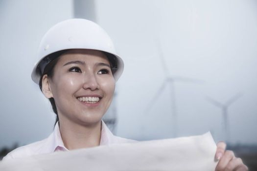 Young smiling female engineer holding a blueprint with wind turbines in the background