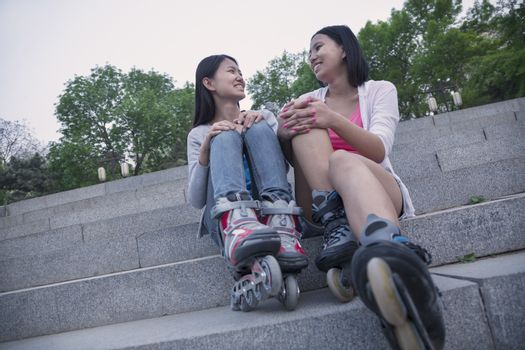 Two young friends with roller blades sitting and resting on concrete steps outdoors