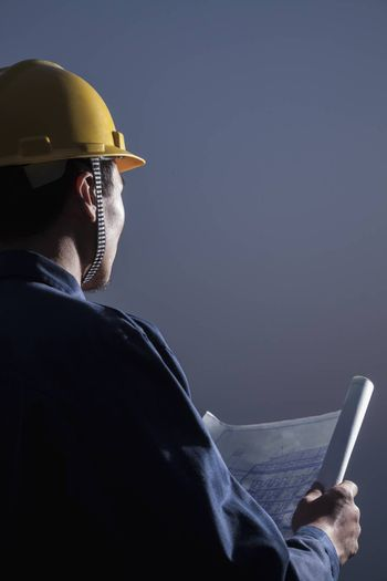 Young male engineer in a hardhat holding a blueprint at dusk, rear view